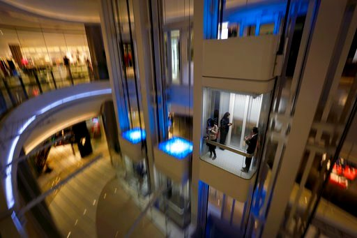 (AP Photo/Andy Wong). Women take an elevator at a newly opened up-scale shopping mall in Beijing, Tuesday, March 6, 2018. China's top economic official set a robust growth target Monday and promised more market opening and cuts in a bloated steel indus...