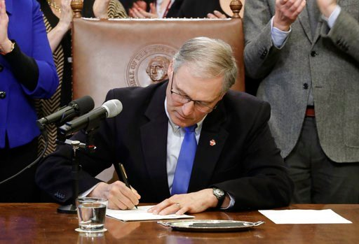 (AP Photo/Ted S. Warren). Washington Gov. Jay Inslee signs a bill Monday, March 5, 2018, in Olympia, Wash., that makes Washington the first state to set up its own net-neutrality requirements.