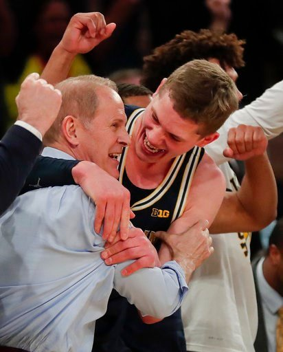 (AP Photo/Julie Jacobson). Michigan head coach John Beilein, left, celebrates with Michigan forward Moritz Wagner (13) after Michigan defeated Purdue 75-66 to win the NCAA Big Ten Conference tournament championship college basketball game, Sunday, Marc...
