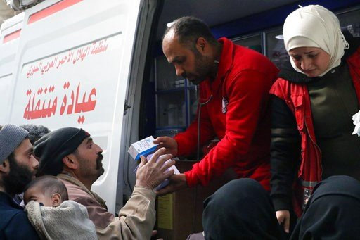 (Syrian Red Crescent via AP). This photo release by the Syrian Red Crescent, shows members of the Syrian Red Crescent distributing medicines for civilians in Douma, eastern Ghouta, a suburb of Damascus, Syria, Monday, March. 5, 2018. Desperate for food...