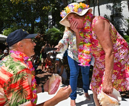 (Rob O'Neal/Florida Keys News Bureau via AP). In this photo provided by the Florida Keys News Bureau, Mary Lou Smith, right, reacts to a surprise marriage proposal from Rick Race after she competed in the Conch Shell Blowing Contest Saturday, March 3, ...