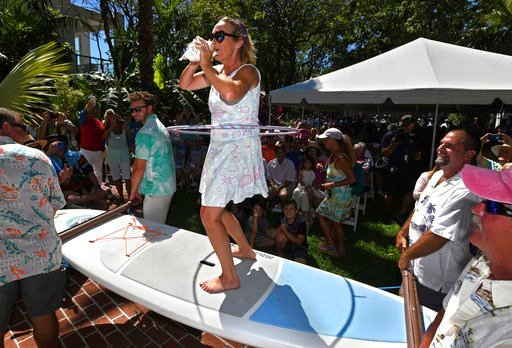 (Rob O'Neal/Florida Keys News Bureau via AP). In this photo provided by the Florida Keys News Bureau, Christine King competes in the Conch Shell Blowing Contest while standing on a paddle board Saturday, March 3, 2018, in Key West, Fla. Judges evaluate...