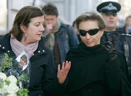 (AP Photo/Alastair Grant, FILE). FILE - In this file photo dated Friday, Nov. 23, 2007, Marina Litvinenko wife of the former Russian intelligence officer Alexander Litvinenko, picture seen on flowers left, who was poisoned by polonium 210, walks with a...