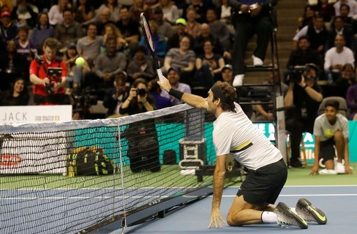 (AP Photo/Jeff Chiu). Roger Federer, of Switzerland, hits from his knees as he plays in an exhibition tennis match with partner Bill Gates against Jack Sock and Savannah Guthrie in San Jose, Calif., Monday, March 5, 2018.
