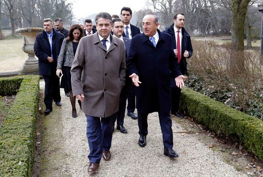 (AP Photo/Michael Sohn). German Foreign Minister Sigmar Gabriel, front left, and his counterpart from Turkey, Mevlut Cavusoglu, front right, walk to take air prior to a meeting in Berlin, Germany, Tuesday, March 6, 2018.