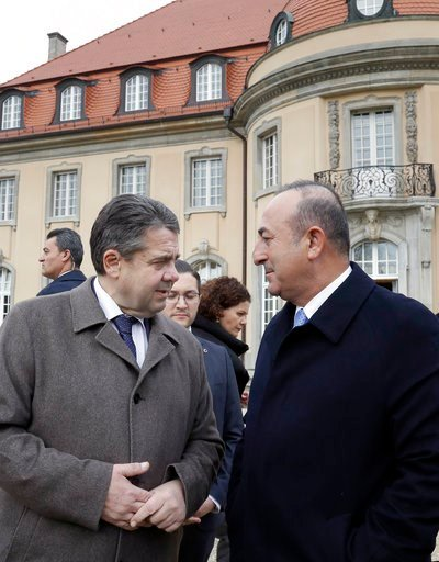(AP Photo/Michael Sohn). German Foreign Minister Sigmar Gabriel, left, and his counterpart from Turkey, Mevlut Cavusoglu, right, walk to take air prior to a meeting in Berlin, Germany, Tuesday, March 6, 2018.