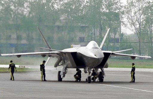 (Color China Photo via AP, File). FILE - In this April 17, 2011 file photo, Chinese ground crew members inspect a J-20 stealth fighter in Chengdu, in southwest China's Sichuan province. China's defense budget will rise 8 percent to 1.1 trillion yuan ($...