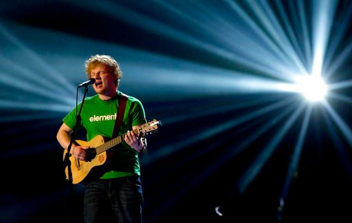 (AP Photo/Joel Ryan). FILE - In this file photo dated Tuesday, Feb. 21, 2012, Ed Sheeran performs during the Brit Awards 2012 at the O2 Arena in London. Organizers said Tuesday March 6, 2018, that a concert by Sheeran at Essen airport in western German...