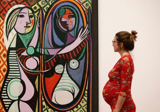(Yui Mok/PA via AP). A woman looking at Pablo Picasso's Girl before a Mirror, 1932, during a preview of the exhibition Picasso 1932 - Love, Fame, Tragedy at Tate Modern in London, Tuesday March 6, 2018.  The first ever solo Pablo Picasso exhibition rem...