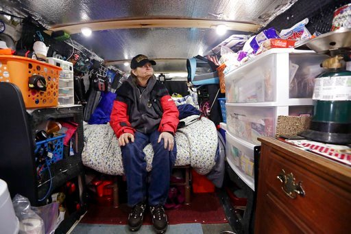 (AP Photo/Elaine Thompson). In this Monday, March 5, 2018, photo, Tamara Bancroft sits inside her van, where she lives with her partner among the two-dozen or so vehicles housing homeless single women in a church parking lot in Kirkland, Wash. Some of ...