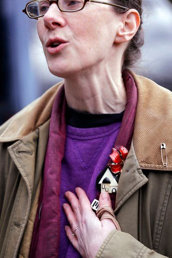(AP Photo/Elaine Thompson). In this Monday, March 5, 2018, photo, Karina O'Malley, who helps manage a car camp for homeless people in the parking lot of Lake Washington United Methodist Church, holds her hand to her heart as she talks with a resident o...