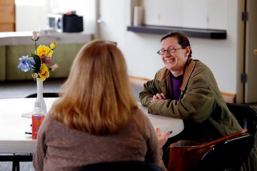 (AP Photo/Elaine Thompson). In this Monday, March 5, 2018, photo, Karina O'Malley, right, who helps manage a car camp for homeless people in the parking lot of Lake Washington United Methodist Church, talks with another volunteer in a day room used by ...