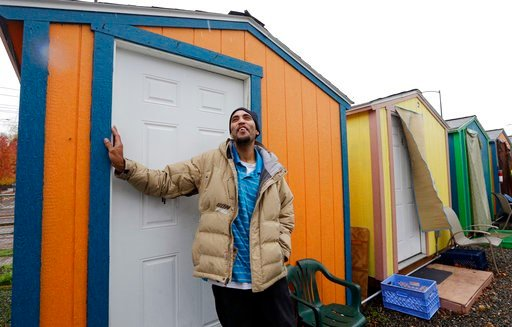 (AP Photo/Elaine Thompson, File). FILE - In this Thursday, Nov. 9, 2017, file photo, Tyson King stands at the door of his tiny house at a homeless encampment in Seattle. In the absence of legislation to incentivize the acceptance of Section 8 vouchers,...