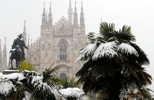 (AP Photo/Antonio Calanni, File). FILE - In this March 2, 2018, file photo, palm trees are dusted in snow after a snowfall in front of Milan's Gothic Cathedral, Italy. New U.S. weather data shows that the Arctic just finished its warmest winter on reco...