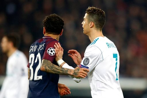 (AP Photo/Francois Mori). PSG's Dani Alves, left, holds Real Madrid's Cristiano Ronaldo during the round of 16, 2nd leg Champions League soccer match between Paris Saint-Germain and Real Madrid at the Parc des Princes Stadium in Paris, Tuesday, March 6...