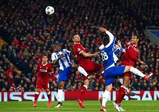 (AP Photo/Dave Thompson). Liverpool's Dejan Lovren, center, attempts a header at goal during the Champions League round of 16, second leg, soccer match between Liverpool and FC Porto at Anfield Stadium, Liverpool, England, Tuesday March 6, 2018.