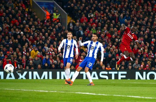 (AP Photo/Dave Thompson). Liverpool's Sadio Mane, right, attempts a shot at goal during the Champions League round of 16, second leg, soccer match between Liverpool and FC Porto at Anfield Stadium, Liverpool, England, Tuesday March 6, 2018.