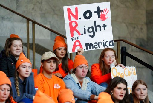 "(AP Photo/Ted S. Warren). Lydia Ringer, 16, a junior at Roosevelt High School in Seattle, holds a sign that reads ""NRA - Not Right for America,"" Tuesday, March 6, 2018, as she attends a rally against gun violence at the Capitol in Olympia, Wash. The ra..."
