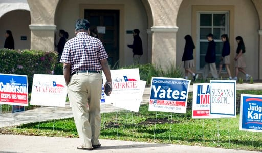 (Brett Coomer /Houston Chronicle via AP). A voter stops to look at primary election signs outside the polling place at St. Anne's Catholic Church on Tuesday, March 6, 2018, in Houston.