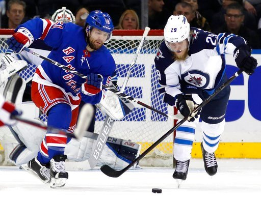(AP Photo/Kathy Willens). Winnipeg Jets right wing Patrik Laine (29) of Finland keeps the puck from New York Rangers center David Desharnais (51) during the third period of an NHL hockey game in New York, Tuesday, March 6, 2018.