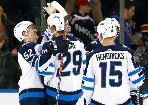 (AP Photo/Kathy Willens). Winnipeg Jets center Jack Roslovic (52) celebrates with Jets right wing Patrik Laine (29) of Finland who had a hat trick after the Jets shut out the New York Rangers 3-0 in an NHL hockey game in New York, Tuesday, March 6, 201...
