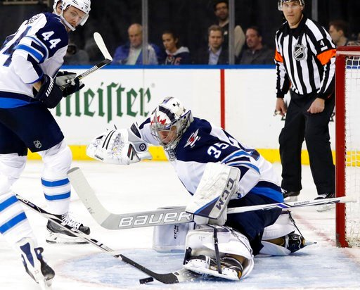 (AP Photo/Kathy Willens). Winnipeg Jets goaltender Steve Mason (35)makes a save with his skate as Winnipeg Jets defenseman Josh Morrissey (44) watches over his shoulder during the second period of an NHL hockey game in New York, Tuesday, March 6, 2018.