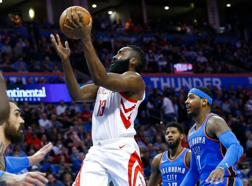 (AP Photo/Sue Ogrocki). Houston Rockets guard James Harden (13) goes up for a shot between Oklahoma City Thunder center Steven Adams, left, forward Paul George (13) and forward Carmelo Anthony (7) in the first half of an NBA basketball game in Oklahoma...