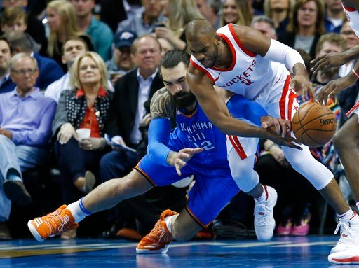 (AP Photo/Sue Ogrocki). Oklahoma City Thunder center Steven Adams, left, reaches to in to knock the ball away from Houston Rockets guard Chris Paul, right, in the first half of an NBA basketball game in Oklahoma City, Tuesday, March 6, 2018.