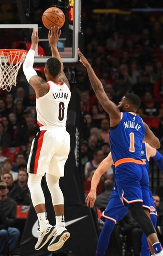 (AP Photo/Steve Dykes). Portland Trail Blazers guard Damian Lillard hits a three point shot over New York Knicks guard Emmanuel Mudiay during the first half of an NBA basketball game in Portland, Ore., Tuesday, March 6, 2018.