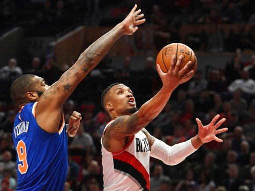 (AP Photo/Steve Dykes). Portland Trail Blazers guard Damian Lillard drives to the basket on New York Knicks center Kyle O'Quinn during the second half of an NBA basketball game in Portland, Ore., Tuesday, March 6, 2018. Lillard scored 37 points as the ...