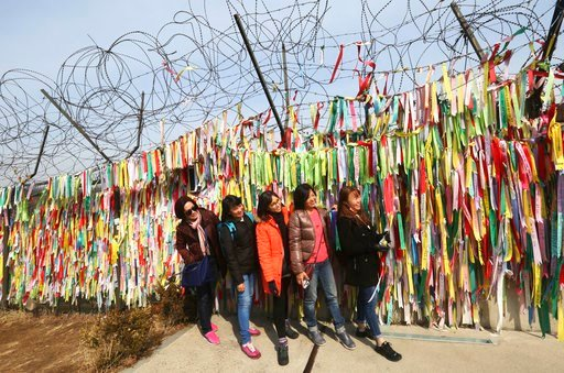 (AP Photo/Ahn Young-joon). Visitors pose in front of ribbons placed on a barbed wire fence with messages wishing for the reunification of the two Koreas at the Imjingak Pavilion in Paju, near the border with North Korea, South Korea, Wednesday, March 7...