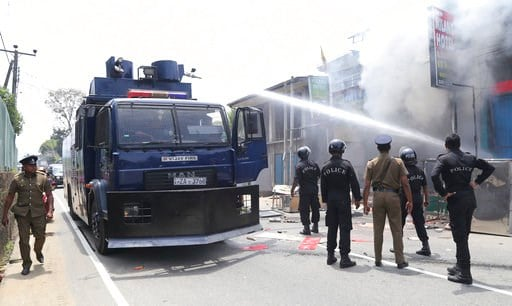 (AP Photo/Rukmal Gamage). Sri Lankan police officers attempt to douse burning shops in Ambatenna, in central Sri Lanka, Wednesday, March 7, 2018. Sri Lanka's president declared a state of emergency Tuesday amid fears that anti-Muslim attacks in several...