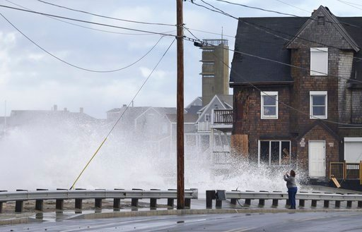 (AP Photo/Elise Amendola). A woman takes pictures of the high surf, Tuesday, March 6, 2018, as waves continue to breach the seawall in Marshfield, Mass. Utilities are racing to restore power to tens of thousands of customers in the Northeast still with...
