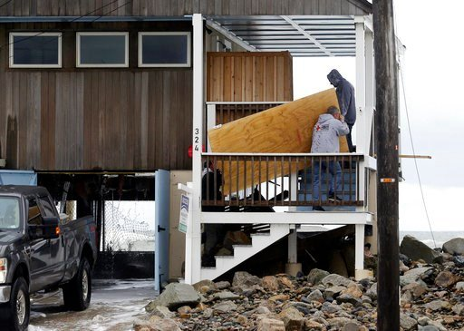 (AP Photo/Elise Amendola). Men work to board up a house, Tuesday, March 6, 2018, along the shore in Marshfield, Mass. Utilities are racing to restore power to tens of thousands of customers in the Northeast still without electricity after last week's s...