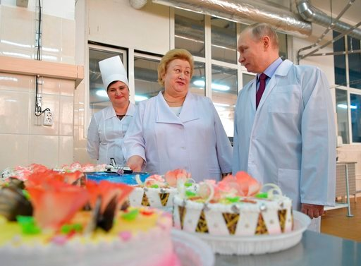 (Alexei Druzhinin, Sputnik, Kremlin Pool Photo via AP). Russian President Vladimir Putin, right, looks at bread and confectionery during his visit to the Samara bakery and confectionery factory on the eve of International Women's Day in Samara, Russia,...