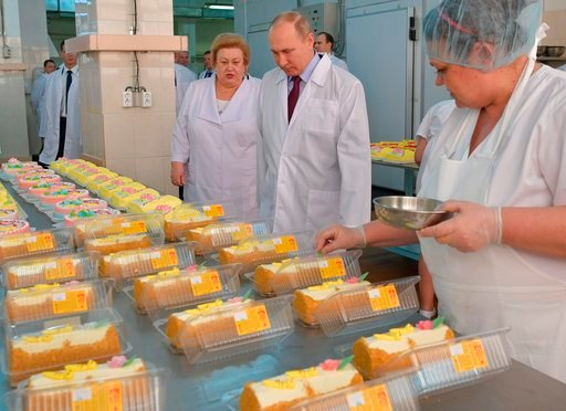 (Alexei Druzhinin, Sputnik, Kremlin Pool Photo via AP). Russian President Vladimir Putin, center, looks at bread and confectionery during his visit to the Samara bakery and confectionery factory on the eve of International Women's Day in Samara, Russia...