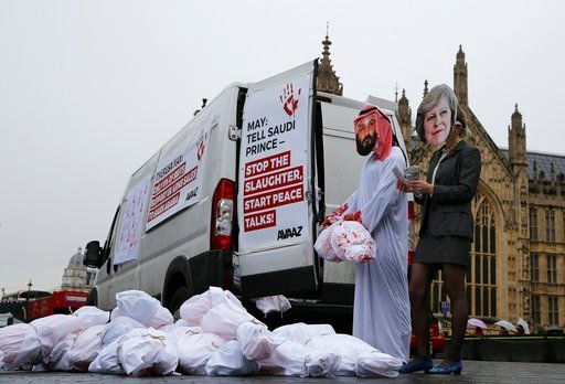 (AP Photo/Alastair Grant). Two protesters wear masks with photographs of Britain's Prime Minister Theresa May and Saudi Crown Prince Mohammad bin Salman outside the Palace of Westminster in London, Wednesday, March 7, 2018, and demonstrate against Brit...