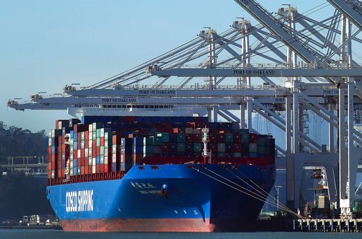 (AP Photo/Ben Margot, File). FILE- In this Jan. 30, 2018, file photo, a container ship waits to be unloaded at the Port of Oakland in Oakland, Calif. The Commerce Department reports on the U.S. trade gap for January, on Wednesday, March 7.