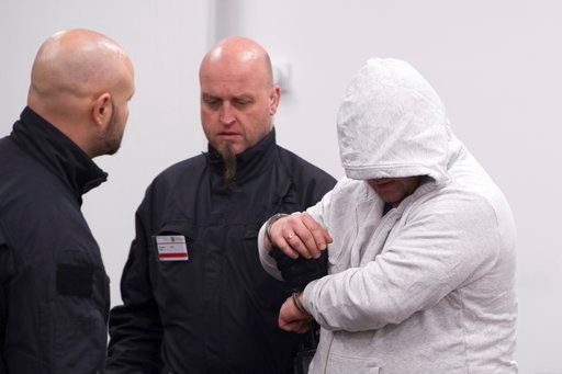(Sebastian Kahnert/dpa via AP,file). In this Jan. 17, 2018 file photo. Mike S. , right, arriving to courtroom ahead of the start of the trial in Dresden, Germany. The German court on Wednesday March 7, 2018 sentenced eight Germans to between four and t...
