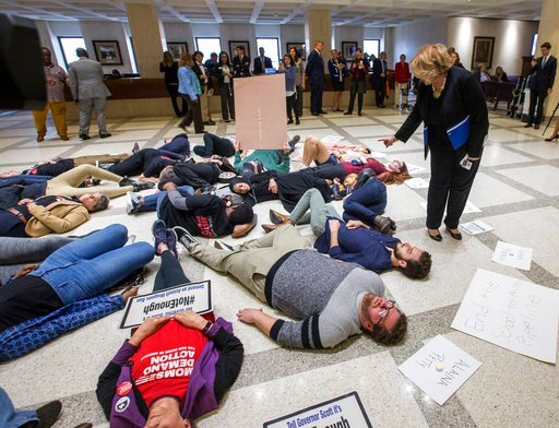 (AP Photo/Mark Wallheiser). Florida Rep. Janet Cruz (D-Tampa) walks around a group of 20 college students and activists as they stage a die-in on the 4th floor rotunda between the House and Senate chambers while the House takes up the school safety bil...