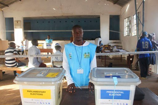 (AP Photo/Kabba Kargbo). An electoral official stands next to empty ballot boxes before a presidential elections, in Freetown, Sierra Leone, Wednesday, March 7, 2018. Sierra Leone's voters are choosing a new president Wednesday from among 16 candidates...