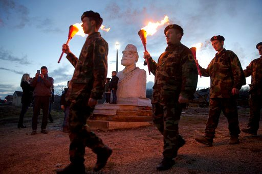 "(AP Photo/Visar Kryeziu). Kosovo Albanians carry flaming torches as they visit the compound of Jashari family houses damaged in 1998/99 Kosovo war during a bonfire ceremony ""Night of the Fires"" in the village of Prekaz, Kosovo on Wednesday, March 7, 20..."