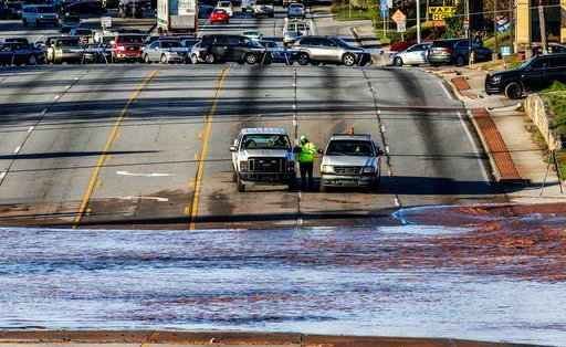 (John Spink/Atlanta Journal-Constitution via AP). Vehicles are stopped by a water main break in Doraville, Ga., Wednesday, March 7, 2018. The massive water main break Wednesday morning left residents outside Atlanta without water, sent water gushing in...