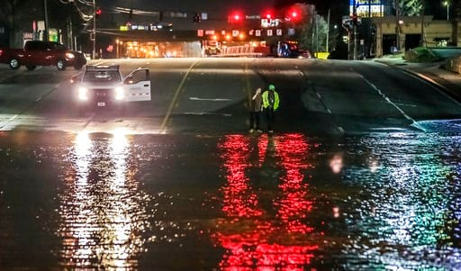 (John Spink/Atlanta Journal-Constitution via AP). People stand near a water main break in Doraville, Ga., Wednesday, March 7, 2018. The massive water main break Wednesday morning left residents outside Atlanta without water, sent water gushing into nei...