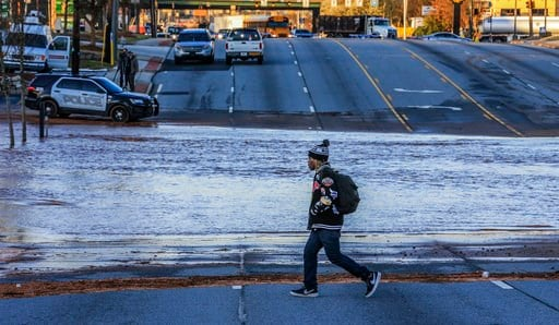 (John Spink/Atlanta Journal-Constitution via AP). A man walks near water from a water main break in Doraville, Ga., Wednesday, March 7, 2018. The massive water main break Wednesday morning left residents outside Atlanta without water, sent water gushin...