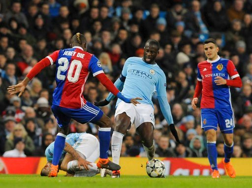 (AP Photo/Rui Vieira). Manchester City's Yaya Toure, center, challenges for the ball with Basel's Geoffroy Serey Die, left, during the Champions League, round of 16, second leg soccer match between Manchester City and Basel at the Etihad Stadium in Man...