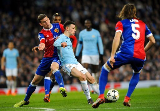 (AP Photo/Rui Vieira). Basel's Fabian Frei, left, challenges for the ball with Manchester City's Phil Foden, center, during the Champions League, round of 16, second leg soccer match between Manchester City and Basel at the Etihad Stadium in Manchester...