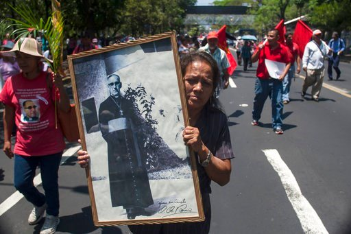 (AP Photo/Salvador Melendez). FILE -- In this March, 24, 2015 file photo, Maria del Pilar Perdomo, 58, holds up a framed portrait of slain Archbishop of San Salvador, Oscar Arnulfo Romero, during a procession to mark the 35th anniversary of his assassi...