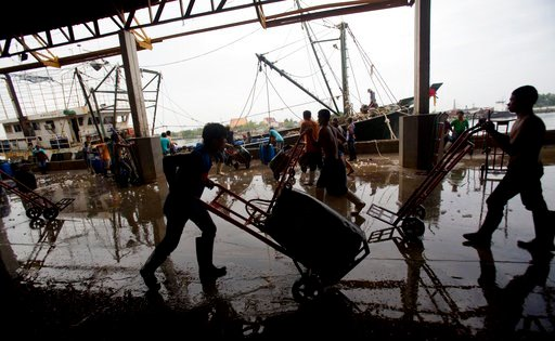 (AP Photo/Sakchai Lalit, File). FIEL - In this June 20, 2014, file photo, migrant workers unload frozen fish from a boat at a fish market in Samut Sakhon Province, west of Bangkok. Thailand's fishing and seafood industry has made some improvement in wo...