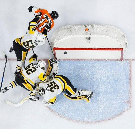 (AP Photo/Matt Slocum). Philadelphia Flyers' Travis Konecny (11) scores a goal past Pittsburgh Penguins' Kris Letang (58), Carl Hagelin (62) and Tristan Jarry (35) during the second period of an NHL hockey game, Wednesday, March 7, 2018, in Philadelphia.